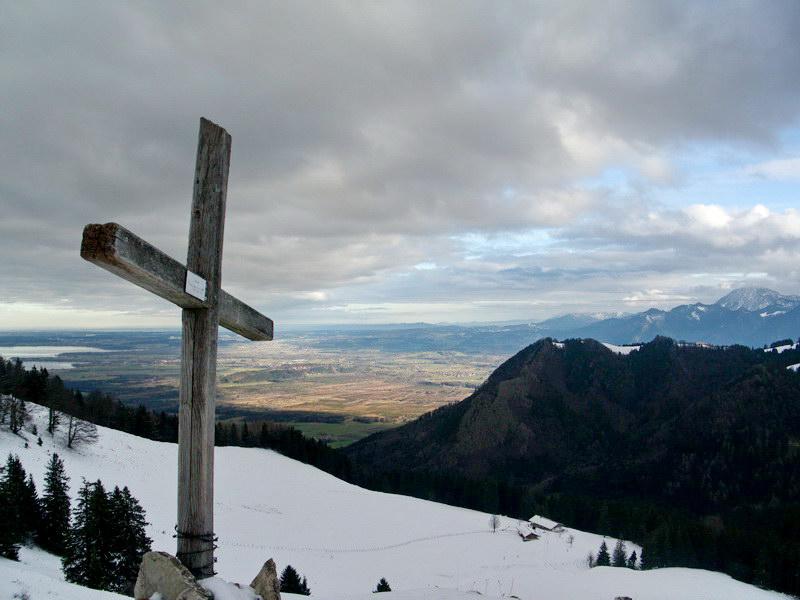Vom schlichten, hölzernen Gipfelkreuz haben wir eine unerwartet schöne Aussicht in den Chiemgau.