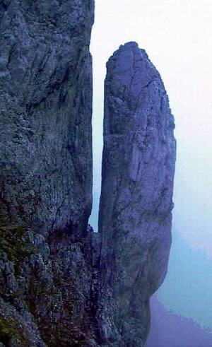 Die Kaindl-Stewart-Nadel vom Kopftörl aus. Mitten in der Scharte zwischen Massiv Vorderer Karlspitze und der Nadel befindet sich der letzte Teil des Steigs, der auf dem Foto gerade von einem Bergsteiger durchquert wird. Der 20 Meter hohe Turm wurde erstmals 1904 durch E. Tatzel und Führer J. Kostner erstiegen.