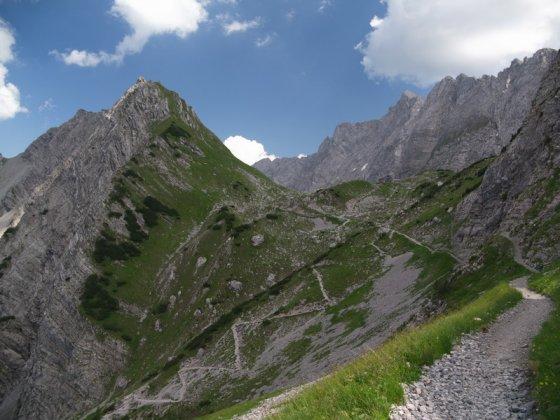 Die Lamsenjochhütte in der Bildmitte. Links darunter sieht man den Aufstiegsweg in vielen Kehren von der Gramaialm. Der Hochnissl ist der sonnenbeschienene Gipfel genau zwischen mittleren und rechten Bilddrittel. Aufnahmestandort ist das westliche Lamsenjoch.
