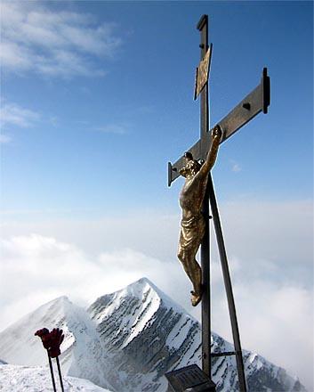Das Gipfelkreuz des Sonntagshorns, im Hintergrund die Reifelberge.