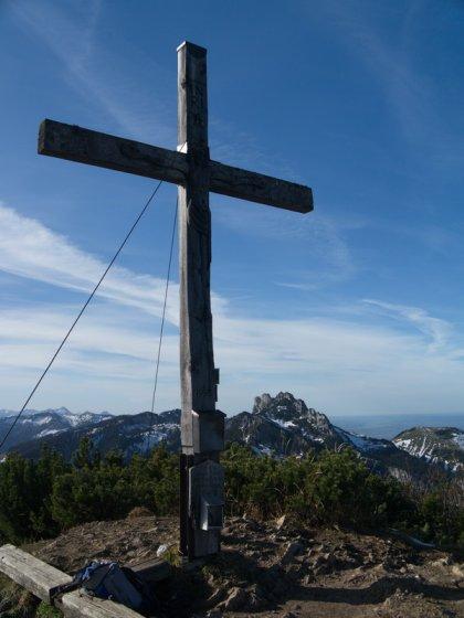 Das Gipfelkreuz der Hochplatte, im Hintergrund die Kampenwand.