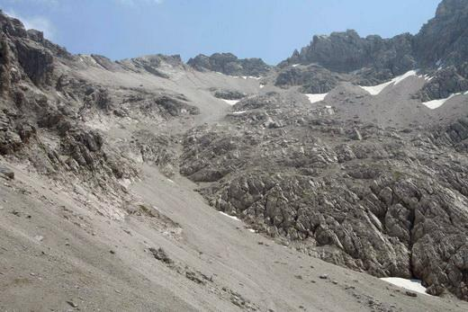 Das Schotterkar, durch das man sich zum Gipfel hochquälen muss. Der Gipfel selbst ist die unscheinbare Erhebung in Bildmitte oben. Rechts davon die Einschartung, auf die man zielt. Rechts ist auch der große Felsriegel zu sehen den man überwinden muss. Etwas links von der Bildmitte die Rinne, die das obere mit dem unteren Schotterfeld verbindet.