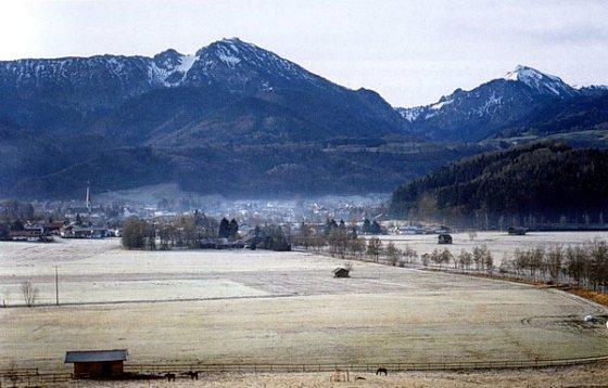Der Hochfelln von Berghaupten aus gesehen. Links davor liegt der Ort Bergen mit seinem spitzen Kirchturm. Der Schneerest im Kar in der Nordflanke zeigt die Lage des ehemaligen Lokalgletschers an, der seine Endmoränen auf der Brünndling-Alm niedergelassen hat.