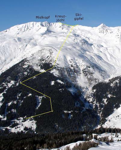 """Das Pfoner Kreuzjöchl - hier gesehen vom Naviser Kreuzjöchl - genau in der Bildmitte. Die gelbe Linie zeigt den ungefähren Aufstiegsweg. Ziemlich genau unterhalb des Gipfels, an der Grenze zwischen der Schneefläche und der darunter liegenden schwachen Aufforstung, sieht man ein Gebilde in der Form eines auf den Kopf gestellten """"V"""". Dieses ist ein großer Zaun direkt beim Wetterkreuz, der die Tourenfahrer davon abhalten soll, in die darunter liegende noch junge Aufforstung zu fahren. Früher war hier die Abfahrt ins Tal möglich, heute ist sie verboten.Pfoner und Naviser Kreuzjöchl liegen sich gegenüber und werden durch das Navistal getrennt."""