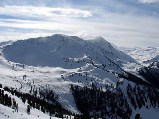 Die Schneegrubenspitze, hier vom nördlich gelegenen Steinbergstein. Der lange Grat bis zum Gipfel ist im linken Drittel des Bildes deutlich erkennbar. Das Hochtal rechts ist das Gebiet der Neuen Bamberger Hütte. Mitte Hintergrund das Kröndlhorn.