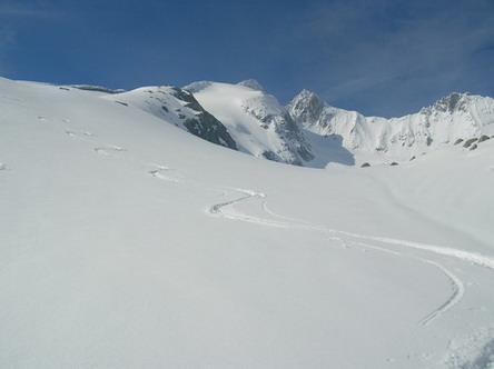 Gabler (Bildmitte) und Reichenspitze (rechts daneben) bei Postkartenwetter. Die Route führt vom Standort des Photographen zunächst nach links oben, dann hält man auf den am Übergang zum Horizont gut sichtbaren Felsenkamms zu (Zielpunkt etwa eine viertel Bildbreite vom linken Bildrand entfernt) und quert knapp unterhalb diesem nach rechts zum Gipfelhang des Gablers. Die letzten achtzig Höhenmeter zum felsigen Gipfel müssen zu Fuß zurückgelegt werden.  Das Bild entstand Mitte Juni, als auf den klassischen Kitzbüheler Skibergen der Bergfrühling bereits in vollem Gange war. Neuschneefälle während eines vorausgegangenen Kälteeinbruchs haben der Szenerie einen hochwinterlichen Anstrich verpaßt.