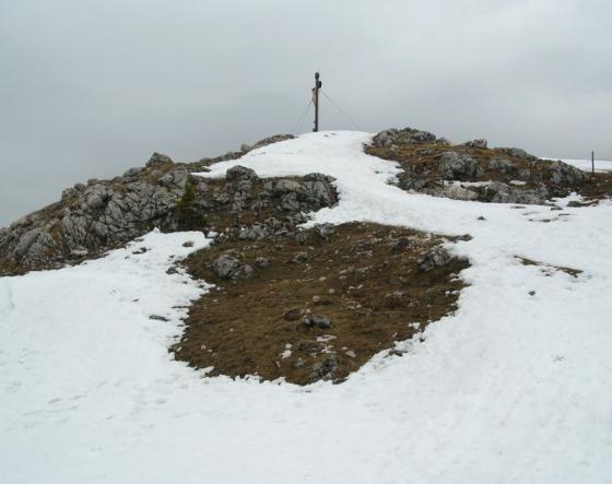 Der Westgipfel des Breitensteins mit seinem schönen Gipfelkreuz.  Die Aufnahme entstand im Spätwinter, als der Schnee bereits knapp wurde. Aufgrund seiner Randlage bekommt der Breitenstein vergleichsweise wenig Niederschläge ab. Daher ist die Skitourenzeit meist auf den Hochwinter beschränkt.