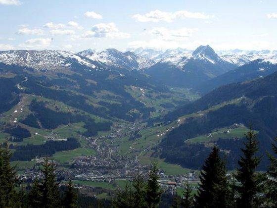 Gipfelblick hinunter nach Kirchberg und dahinter in das Spertental. Im rechten Bilddrittel dominiert der große Rettenstein, links dahinter (zum Teil in Wolken) der Großvenediger.