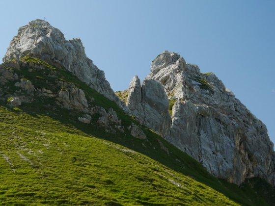 Vom Krahnsattel aus der Blick auf den Vorgipfel Hexenstein (links) und auf die Nordwand der Haidachstellwand (rechts). Hier sind einige Kletterer auf dem Klettersteig zu erkennen.