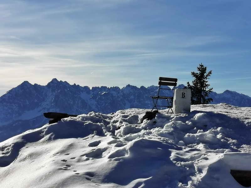 Auf dem Sonnwendköpfl steht ein Grenzstein, dahinter erheben sich die höchsten Spitzen des Wilden Kaisers.
